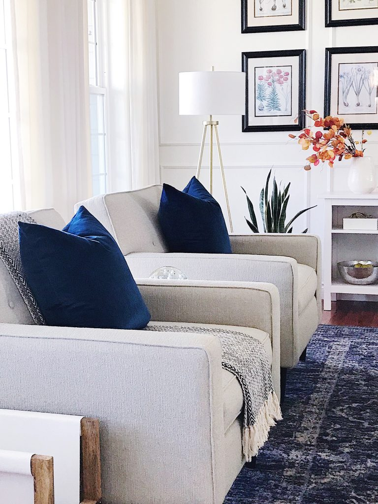 Two armchairs in the living room with tripod lamp, velvet pillows, blue vintage rug, white walls with molding and framed botanical prints #livingroomdecor
