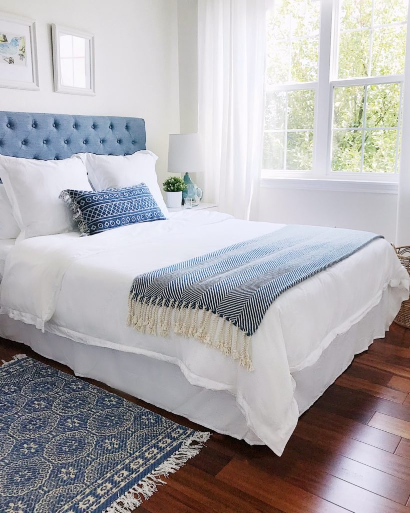 Blue and white bedroom with blue upholstered headboard, blue Serena and Lily throw with fringe, boho pillow and rug, and white curtains - how to choose a design style - jane at home - a cozy haven for guests
