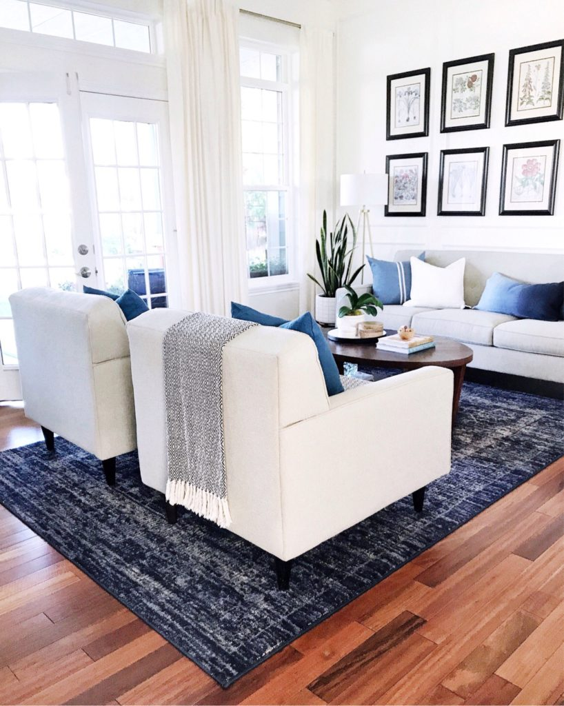 Living room decor with blue vintage distressed rug, modern furniture, large windows and French doors, blue pillows, and botanical framed prints - how to choose a design style - jane at home