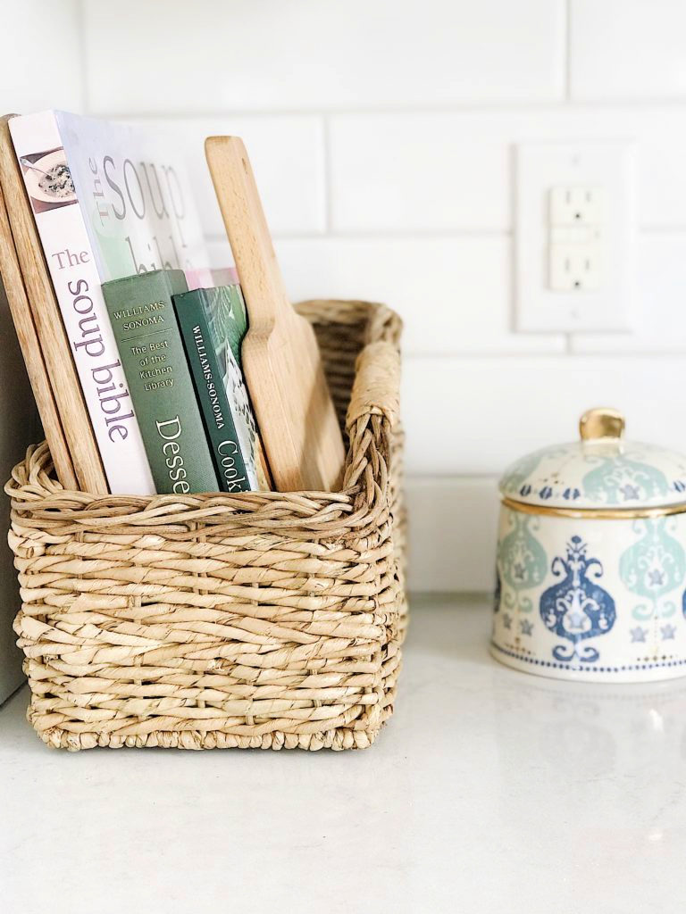 Getting organized and decluttering the kitchen with baskets for cookbooks, cutting boards and gilded Diana canister