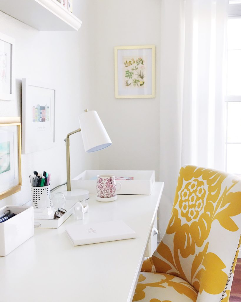 Light and bright office space with yellow chair, white desk and lamp, open shelving and pink mug