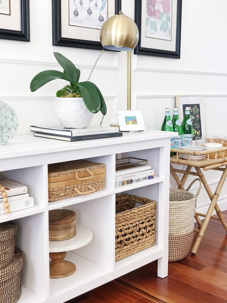 White shelf decor styled with baskets, plants, books and artwork, along with a bamboo bar cart