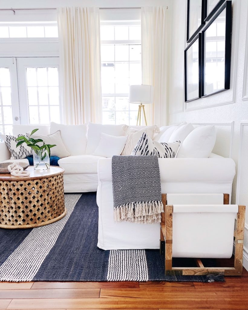 A white slipcovered sectional sofa and striped rug add a touch of relaxed summer style to our living room - jane at home #decor #design #ideas #style