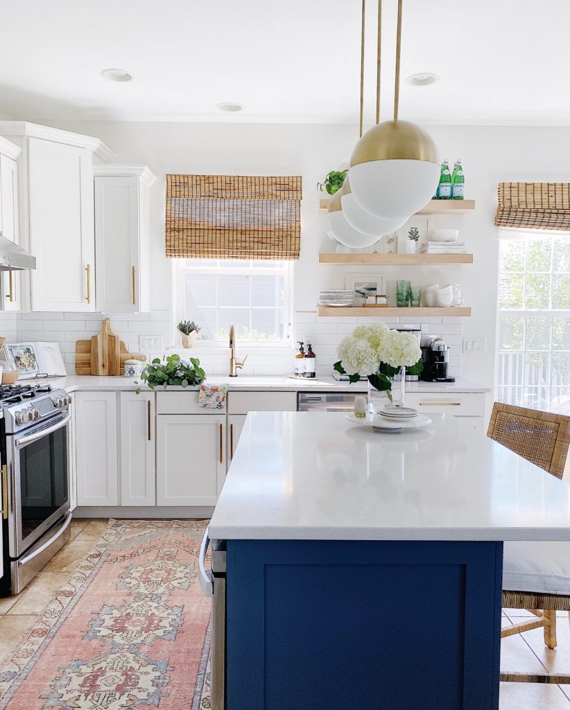 How to find your design style - blue and white kitchen with oushak rug and woven counter stools - jane at home #kitchendesign #bluekitchen #kitchenideas #designstyle