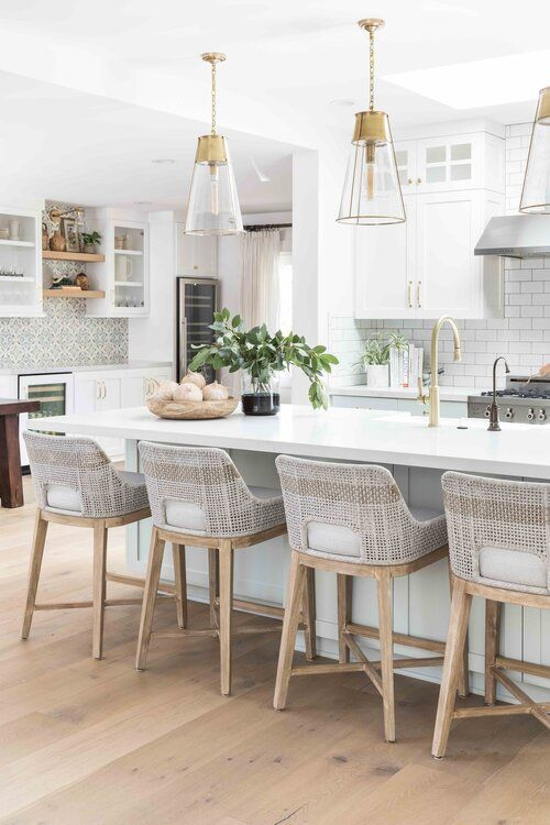 Modern coastal kitchen with woven counter stools and glass pendant lights