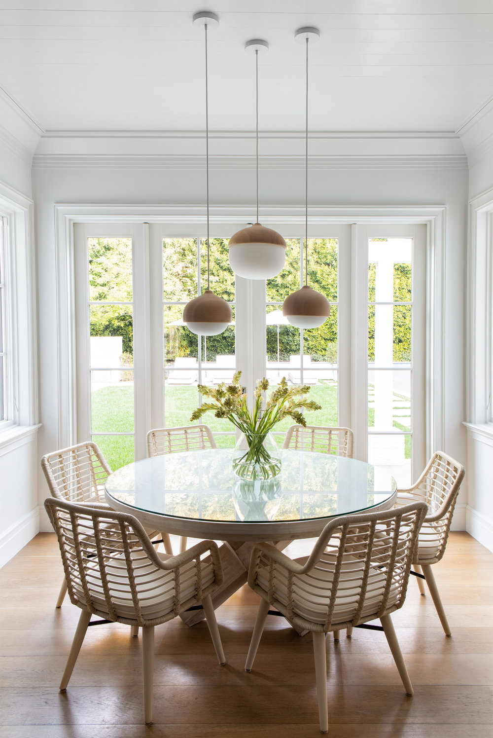 Beautiful breakfast nook / kitchen dining area with woven chairs and modern pendant lights Chango & co