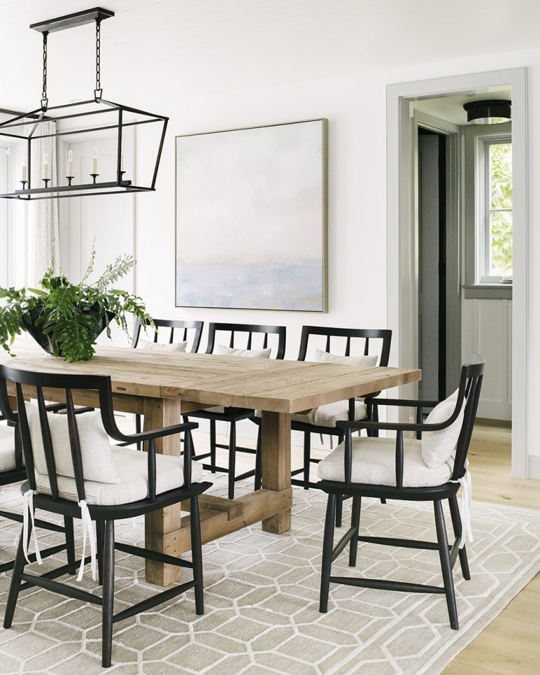 Modern dining room with rustic wood table, black chairs and lantern light, and modern coastal artwork
