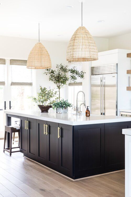 Stunning modern kitchen with black island, white cabinets and beach house style pendant lights over the island