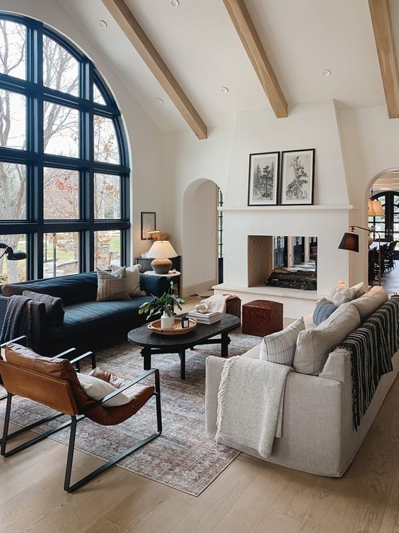 Design and decor trends for 2021: Beautiful closed concept living room design with see through fireplace, arched windo and wood beamed ceiling - Chris Loves Julia