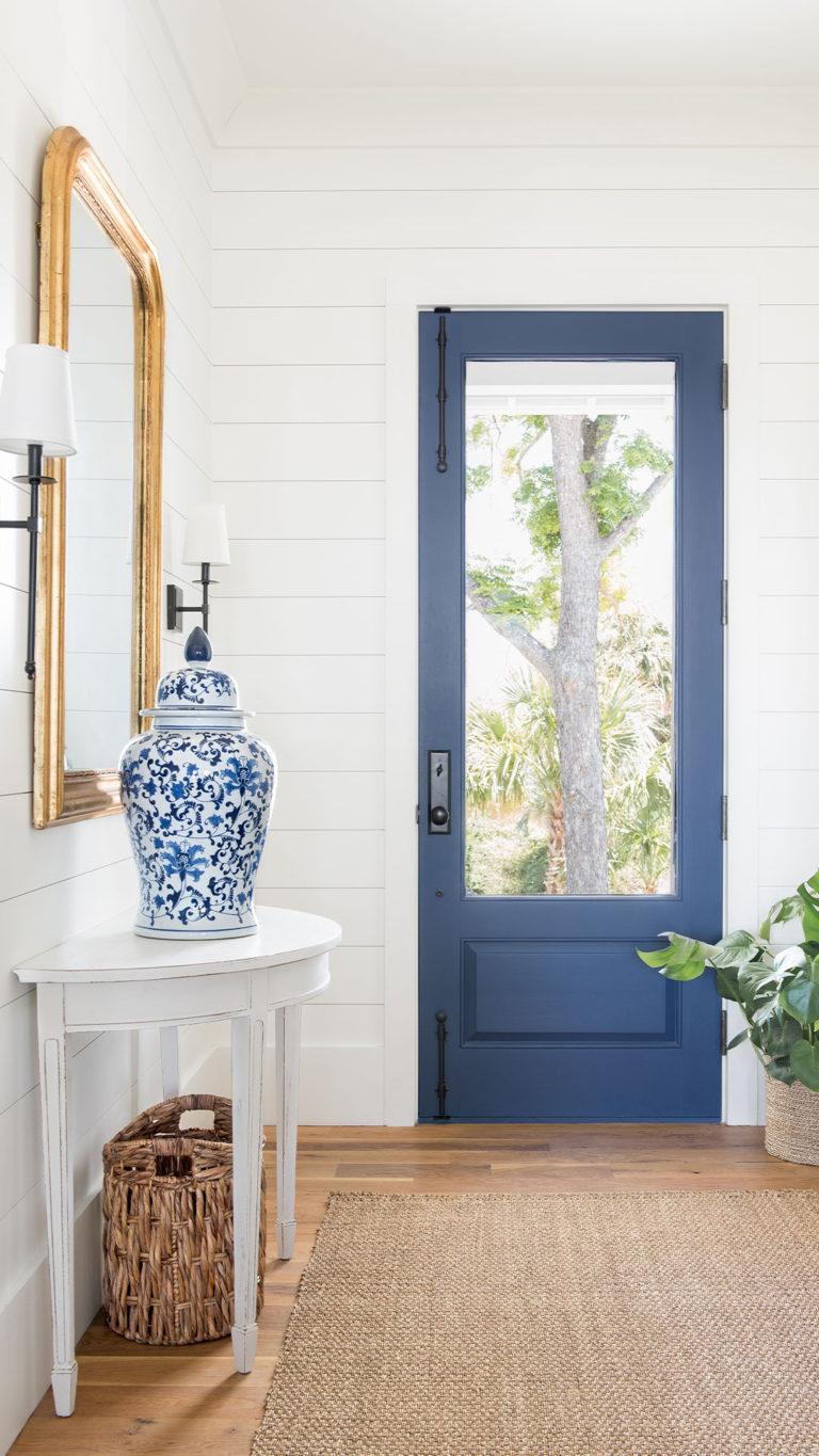 Shiplap walls, a natural fiber rug, and a glorious blue door create the quintessential coastal entryway. From Barrow Building Group.