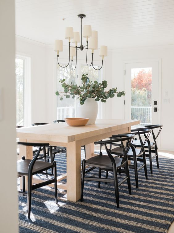 Design and decor trends for 2021: Beautiful multi-functional dining room with striped rug and black wishbone side chairs