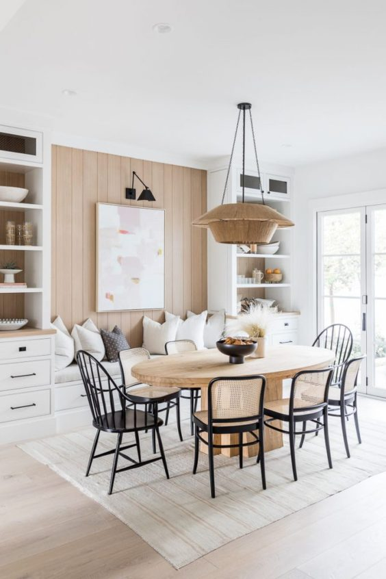 Design and decor trends for 2021: Beautiful dining room with warm tones, woven light fixture, cane chairs, and oval table