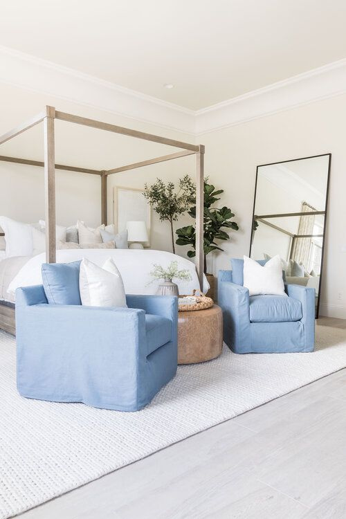 Beautiful modern master bedroom with wood canopy bed, beach house styling and seating area with blue chairs