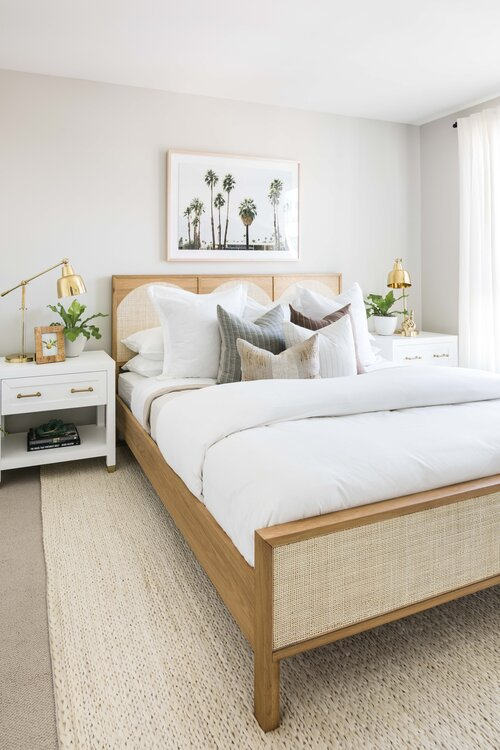Gorgeous boho bedroom with layered bedding and pillows and modern beach house decor - Pure Salt Interiors