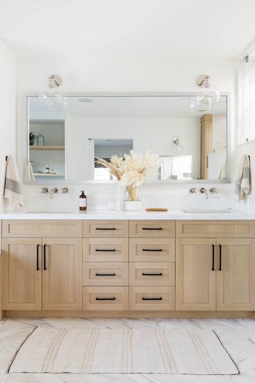Beautiful bathroom inspiration - light wood vanity with black pulls and chrome faucets and sconces