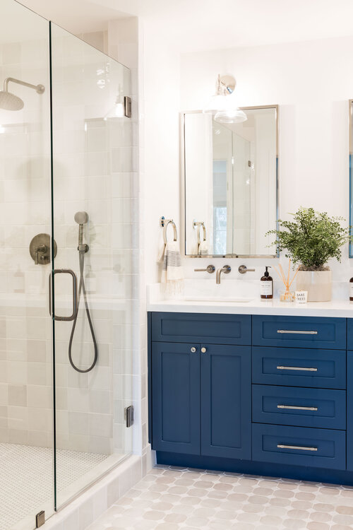 Lovely bathroom with dark navy vanity color and glass shower enclosure