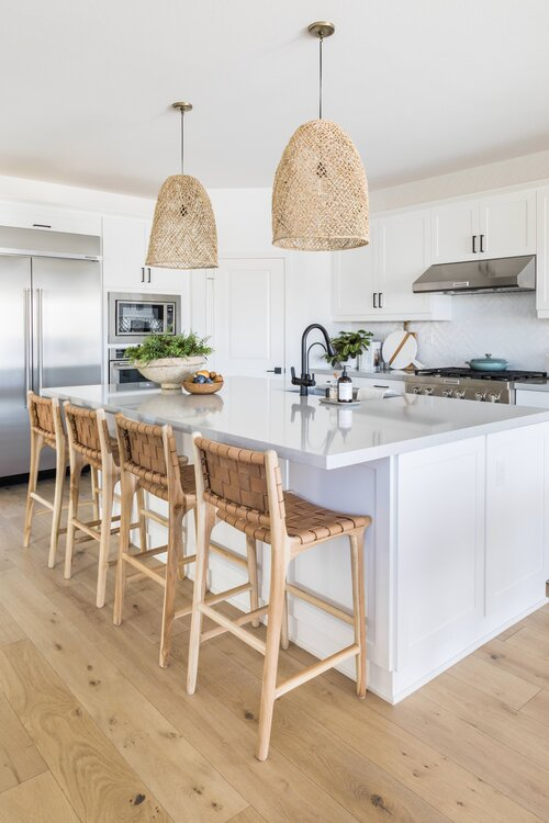 Beautiful beach house kitchen with woven stools and pendant lights over the island