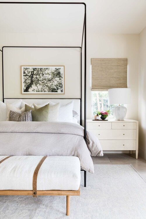 Gorgeous modern master bedroom with black canopy bed and bench at the end of the bed