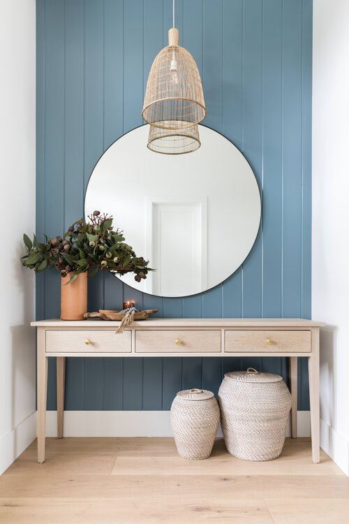 Beautiful modern coastal entryway with round mirror and baskets - beach house decor