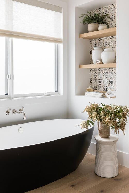 Beautiful black freestanding tub and built in shelves and storage in the master bathroom