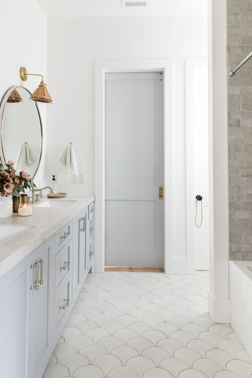 Love this beautiful master bathroom with light blue gray vanity, double sinks and scale patterned floor tile!