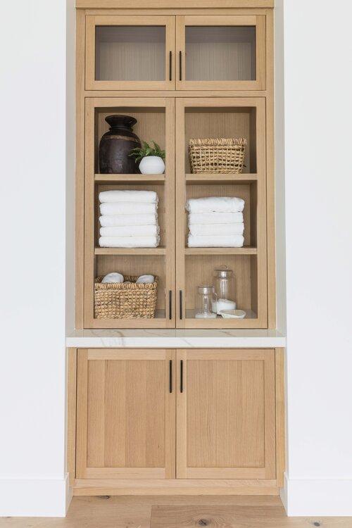 Gorgeous modern master bathroom with built in light wood linen cabinet - Pure Salt Interiors