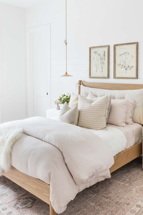 Lovely boho bedroom with layered bedding, floral artwork and neutral decor