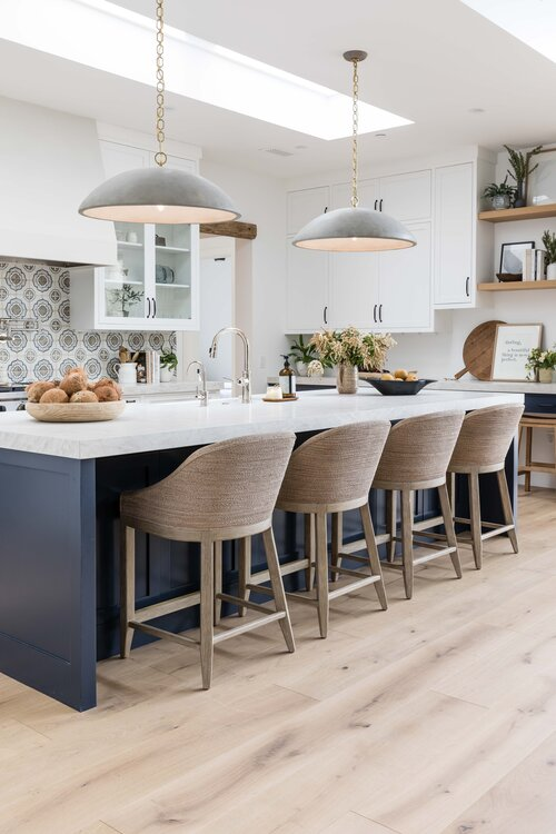 Gorgeous modern kitchen with dark blue island, woven counter stools and black pendant lights