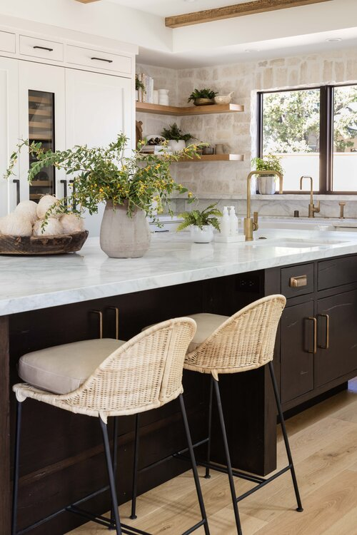 Beautiful modern kitchen design with dark black vanity and woven counter stools - pure salt