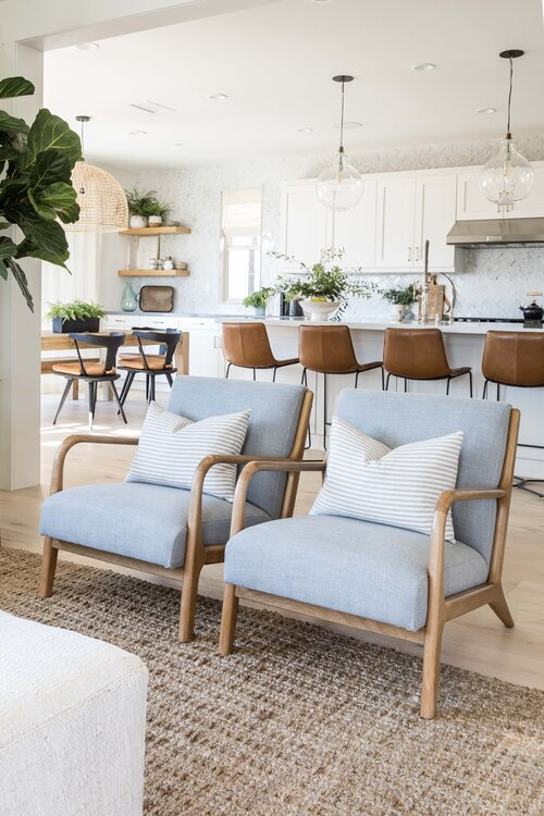 Gorgeous open concept living room and kitchen area with two modern side chairs