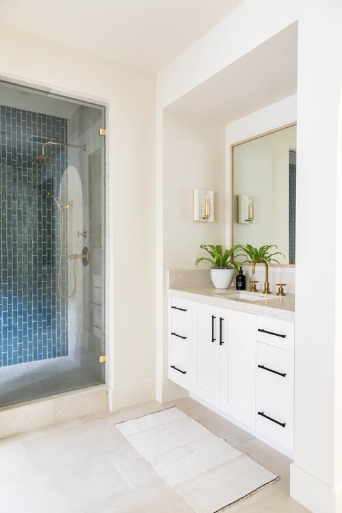 Beautiful master bathroom with blue shower tile and white vanity