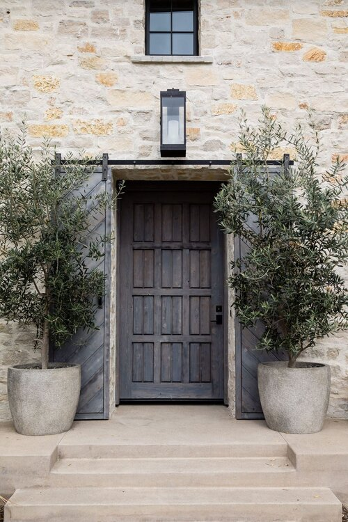 Stunning home exterior with stone entrance, wood door, black lantern lighting and olive trees