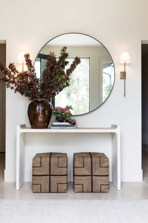 Beautiful modern entryway with console table, round mirror and woven poufs