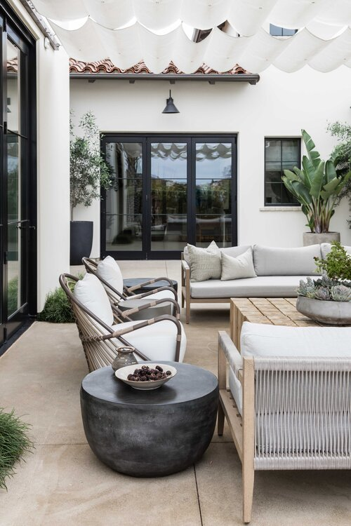Gorgeous outdoor seating area and covered patio with modern furniture and outdoor fireplace - Pure Salt Interiors